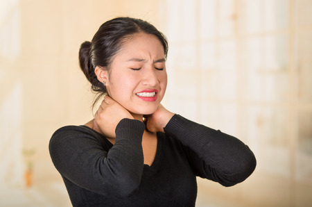 Young hispanic woman posing for camera showing signs of neck pain, holding hands on painful body part, injury concept