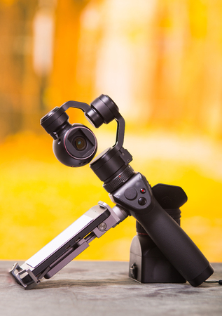 QUITO, ECUADOR- DECEMBER 22, 2017: Osmo Mobile gimbal, new generation of electronic stabilizer over a wooden table in a blurred forest background