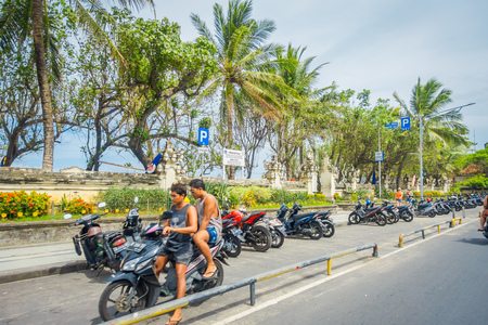 BALI- INDONESIA MARCH 08. 2017: Unidentified motorcyclist rides down the street. Legians area. Legian is a suburban and beach area on the west coast of Bali Editorial