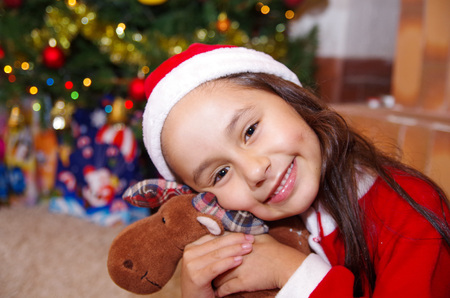 litle: Beautiful smiling litle girl wearing a christmas clothes, hugging a moose teddy, with a christmas tree background with some presents Stock Photo