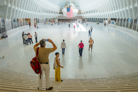 NEW YORK, USA - MAY 05, 2017: Crowds of passengers pass under the distinctive architectural, form of the Oculus transportation hub at World Trade Center, by architect Santiago Calatrava in New York Usa. Editorial