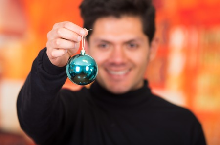 QUITO, ECUADOR- 17 OCTOBER, 2015: Close up of a handsome young man holding in his hands a beautiful and blue ball for christmas tree decoration, wering a black turtleneck sweather.