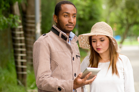 mixed marriage: Beautiful young multi-ethnic couple having fun together at the park, man looking somewhere while woman watching his cellphone