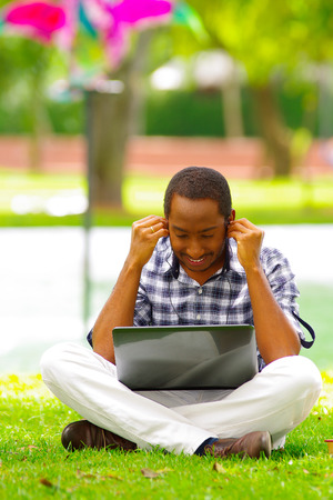 Young black man sitting down on green grass and working in his computer and listening music with his headphones in the city of Quito Ecuador