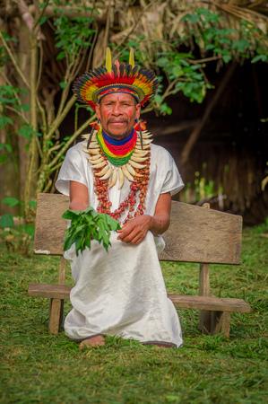 éxtasis: LAGO AGRIO, ECUADOR - 17 DE NOVIEMBRE DE 2016: Shaman de Siona que se sienta en una silla con un vestido tradicional con un sombrero de pluma en un pueblo indígena en la reserva de la fauna de Cuyabeno