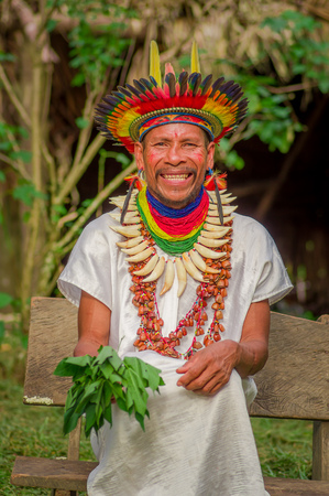LAGO AGRIO, ECUADOR - NOVEMBER 17, 2016: Smiling Siona shaman in traditional dress with a feather hat in an indigenous village in the Cuyabeno Wildlife Reserve Editorial