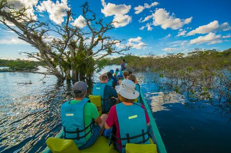 CUYABENO, ECUADOR - NOVEMBER 16, 2016: Unidentified people travelling by boat into the depth of Amazon Jungle in Cuyabeno National Park, Ecuador Editorial