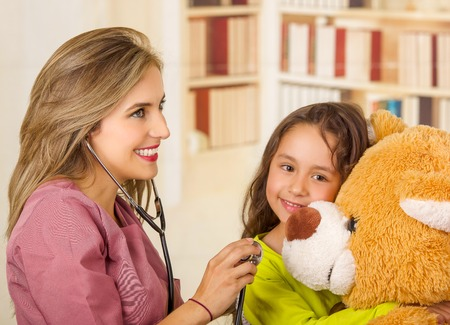 Young pretty girl smiling and hugging her teddy bear while a beautiful smiling doctor examining with a stethoscope in a office background