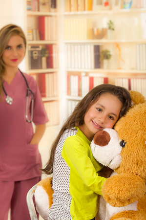 Young pretty girl smiling and hugging her teddy bear in a office background with a burred doctor.