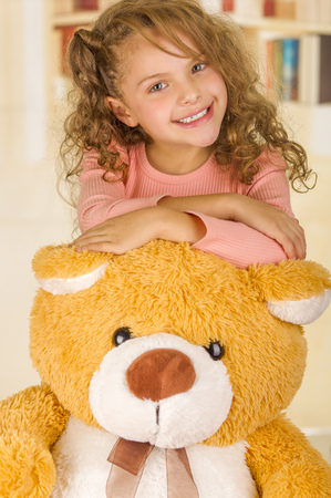bear s: A portrait of a young pretty girl smiling and posing over her teddy bear s head in a doctor office background