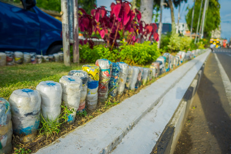 BALI, INDONESIA - MARCH 08, 2017: A plastic water bottles in the park at upside down in row, recycled to adorn parks and avenues, the concept of environmental protection in Denpasar Indonesia