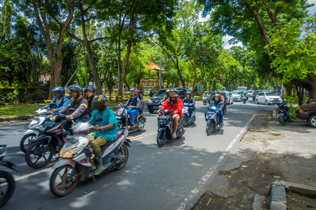 BALI, INDONESIA - MARCH 08, 2017: Unidentified people driving motorcycles and cars in the road full of traffic. The government says Bali streets could be gridlocked in five years with vehicle sales growing by 12.3 percent a year, in Denpasar Indonesia Editorial
