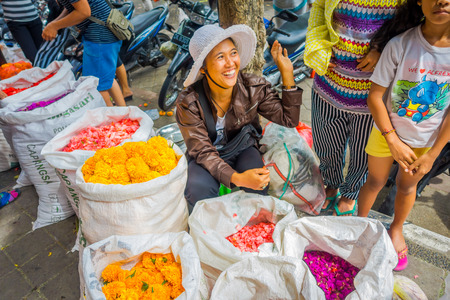 BALI, INDONESIA - MARCH 08, 2017: Unidentified people in outdoors Bali flower market. Flowers are used daily by Balinese Hindus as symbolic offerings at temples, inside of colorful baskets