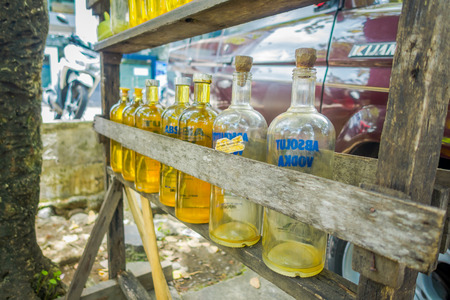 developing country: BALI, INDONESIA - MARCH 08, 2017: Illegal gasoline petrol is sold at the side of the road, recycled glass vodka bottles in Bali, Indonesia