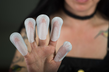 protectors: Close up of young woman wearing nails protector in her nails, hand and ideal clean manicure, in a black background