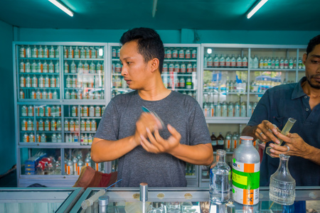 essences: BALI, INDONESIA - MARCH 08, 2017: Unidentified man using syringes and pipettes mixing essences to prepare perfumes for the perfume store in Denpasar Indonesia Editorial