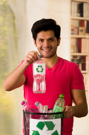 polycarbonate: Smiling young man putting a plastic bottle inside of a small black garbage collector full of plastic, recycle and safe the world from global warming concept Stock Photo