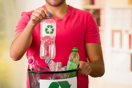 Smiling young man putting a plastic bottle inside of a small black garbage collector full of plastic, recycle and safe the world from global warming concept Stock Photo