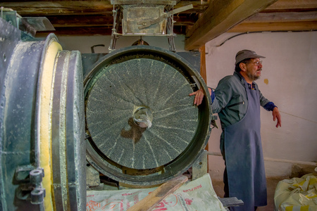 QUITO, ECUADOR - NOVEMBER 23, 2016: Unidentified man working in an old stone grinder mill made to produce flour indoor located in the City of Quito Editorial