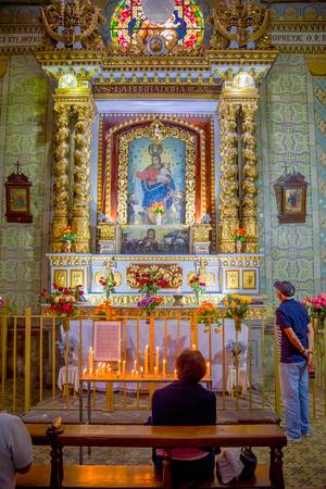 QUITO, ECUADOR - NOVEMBER 23, 2016: Unidentified people praying inside of the Church and Convent of Saint Francis, with chairs an spiritual images