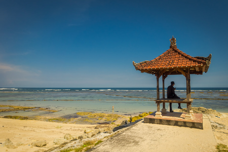 Man wearing a black clothes in a beautiful sunny day under a small cabain in the beach of Pantai pandawa, in Bali island, Indonesia