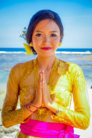 BALI, INDONESIA - MARCH 11, 2017: Beautiful woman in thai traditional dress in the beach of Pantai pandawa, in Bali island, Indonesia