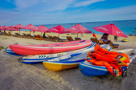 BALI, INDONESIA - MARCH 11, 2017: Beautiful sunny day with a row of red unmbrellas and some boats on the yellow sand, in the beach of Pantai pandawa, in Bali island, Indonesia