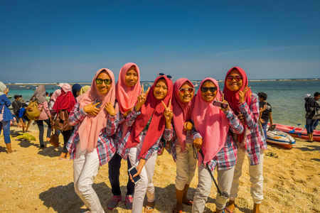 BALI, INDONESIA - MARCH 11, 2017: Unidentified group of women wearing in her heads a pink jiyab and enjoying the beautiful sunny day in the beach of Pantai pandawa, in Bali island, Indonesia Editorial