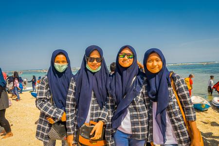 BALI, INDONESIA - MARCH 11, 2017: Unidentified group of women wearing in her heads a dark blue jiyab and enjoying the beautiful sunny day in the beach of Pantai pandawa, in Bali island, Indonesia Editorial