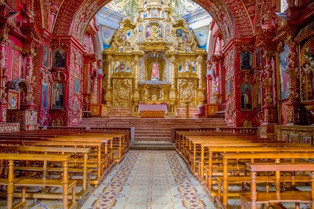 QUITO, ECUADOR - NOVEMBER 23, 2016: Interior of the Church of Santo Domingo, with chairs an spiritual images