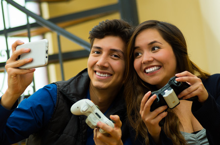 he: Beautiful couple playing video games on the couch holding in their hands a gamepad while he is taking a selfie, concept about home entertainment, video games Stock Photo