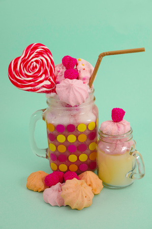 Delicious extreme milkshake of strawberry in a jar, with a blackberry candy over a milk foam with a plastic straw and a pink blackberry candy with a heart candy on top, in a soft blue background