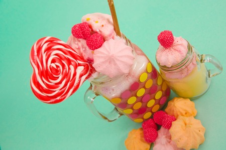 Close up of a delicious homemade extreme milkshake of strawberry in a jar, with a blackberry candy over a milk foam with a plastic straw and a pink blackberry candy with a heart candy on top, in a soft blue background