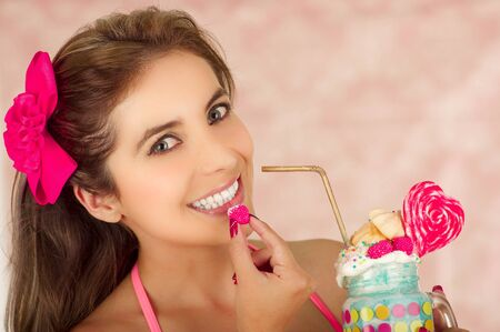 Indoor portrait of pretty cute woman with blackberry in her hand ready eat and holding with her other hand a tasty milk shake in a jar, in a pink background