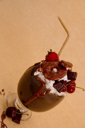 Chocolate indulgent extreme milkshake with brownie cake, strawberries, cherries, and a plastic straw with milk foam on top in a soft brown background Stock Photo