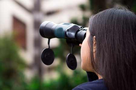 spying: Young woman stalking with a black binoculars in a city background