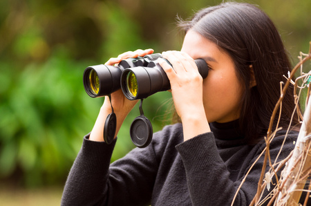 spying: Young woman looking through black binoculars in the forest in a blurred background