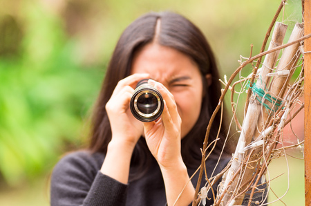 stalker: Young woman looking through black monocular in the forest in a blurred background
