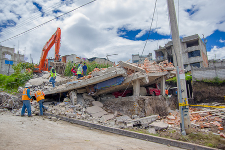 Quito, Ecuador - April,17, 2016: Unidentified group of people looking the house destroyed by Earthquake, and heavy machinery cleaning the disaster in the city of Quito, Ecuador.