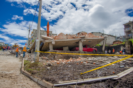 Quito, Ecuador - April,17, 2016: House destroyed by Earthquake, with a red car caught under the destroyed construction, and heavy machinery cleaning the disaster in the city of Quito, Ecuador. Editorial