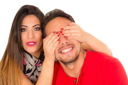 Close up of happy couple isolated on white background. Attractive man and woman being playful, woman putting her hands over his boyfriend eyes Imagens