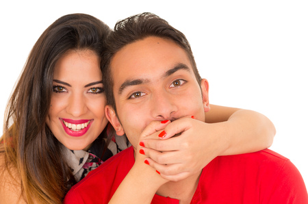 Close up of happy couple isolated on white background. Attractive man and woman being playful, woman putting her hands over his boyfriend mouth Imagens