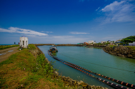 resting: MANABI, ECUADOR - JUNE 4, 2012: Stagnant water with a water pumping machine at Same, Ecuador in a beautiful blue sky in a sunny day Stock Photo