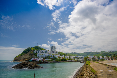 Close up of a rocky beach and buildings behind in a beautiful day in with sunny weather in a blue sky in Same, Ecuador