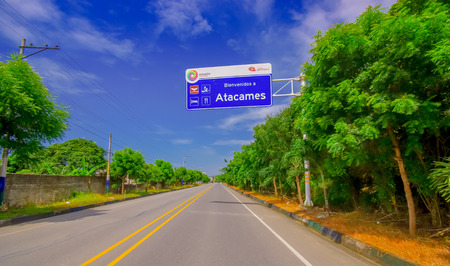 Paved road in the coast, with informative sign, surrounded with abundat vegetation in a sunny day in the Ecuadorian coasts Stock Photo