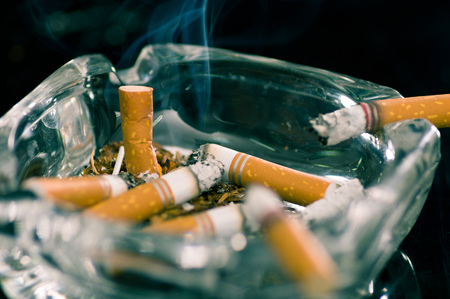 Close up of consumed cigarettes over a crystal ashtray in black background. Stock Photo