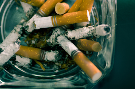 Nahaufnahme von verbrauchten Zigaretten über einem Kristall Aschenbecher. Standard-Bild