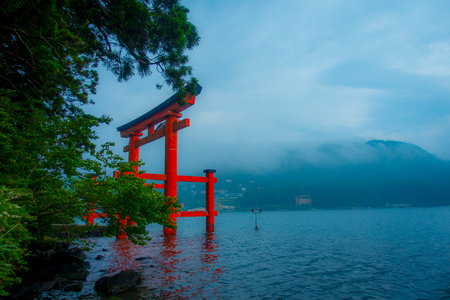 Bright red Torii gate submerged in the waters of Ashi lake, caldera with mountains on the background. Hakone Shrine, Kanagawa prefecture, Japan, in a foggy weather. Stock Photo