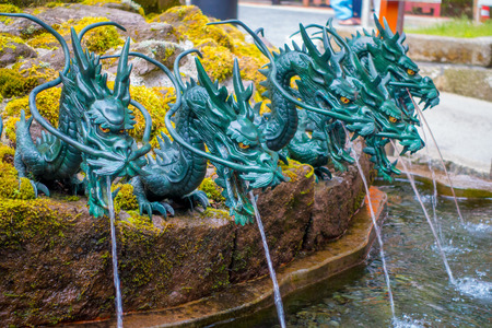 HAKONE, JAPAN - JULY 02, 2017: Close up of a fountain with a bronze dragon in Japan.