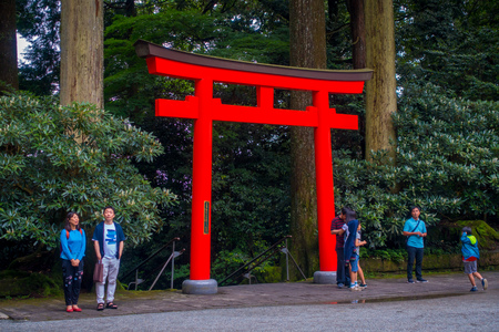 the abbot: HAKONE, JAPAN - JULY 02, 2017: Unidentified people drinking water at the enter of red Tori Gate at Fushimi Inari Shrine in Kyoto, Japan.